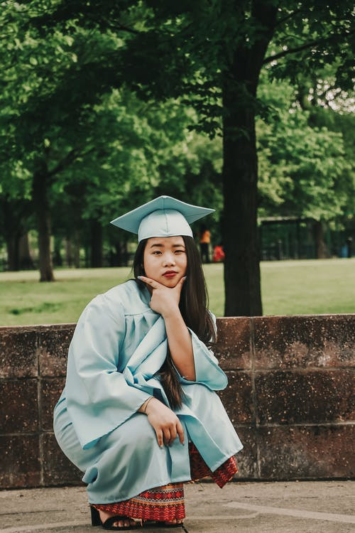 Crouching Woman Wearing Blue Academic Gown and Hat