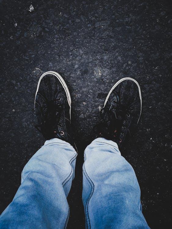 Person in Pair of Black Low-top Sneakers