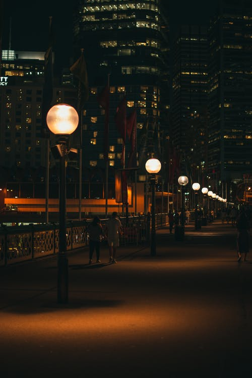 Turned On Lamp Posts Beside High-rise Buildings At Night
