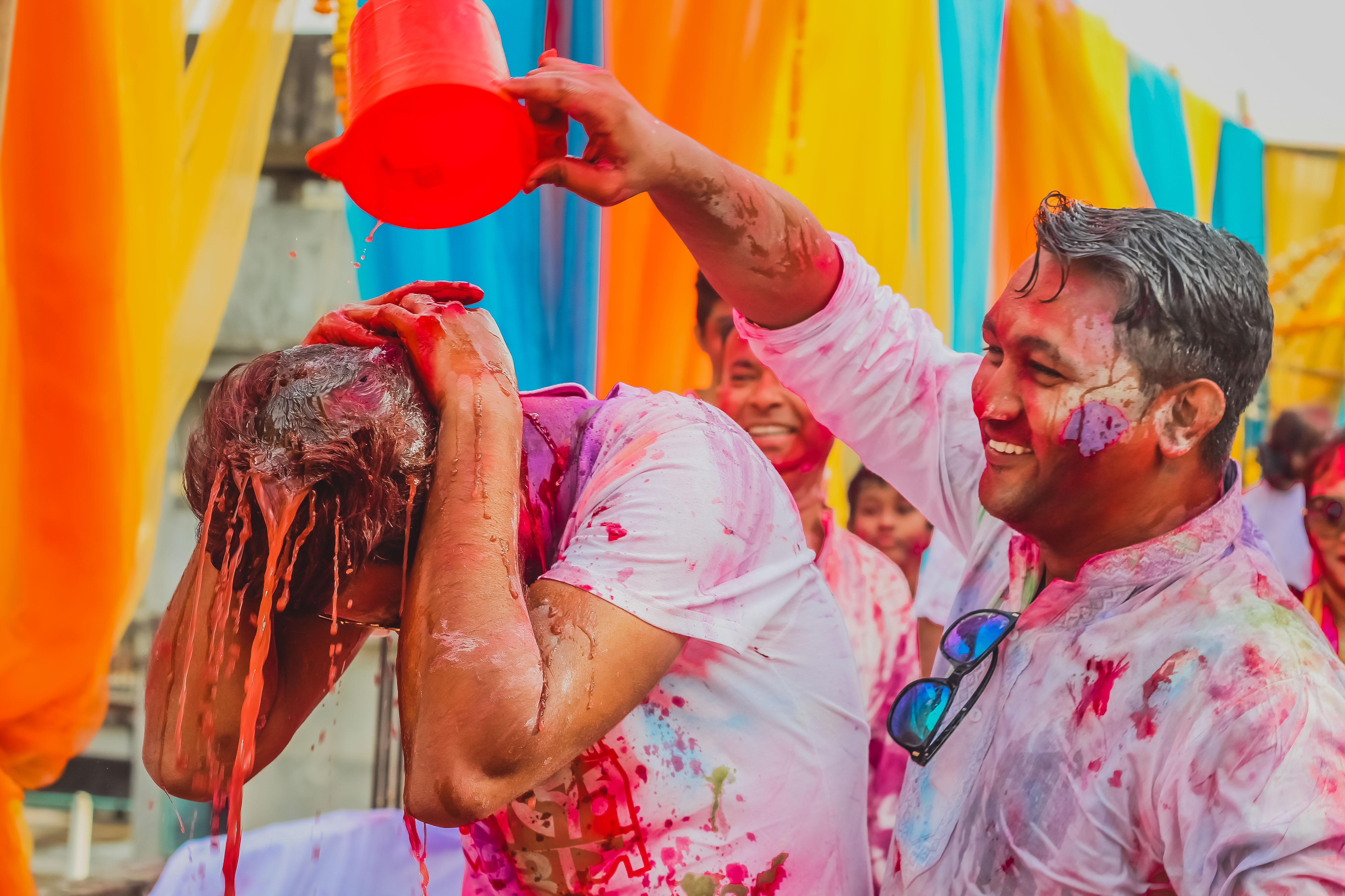 Man Pouring Colored Liquid to Another Man