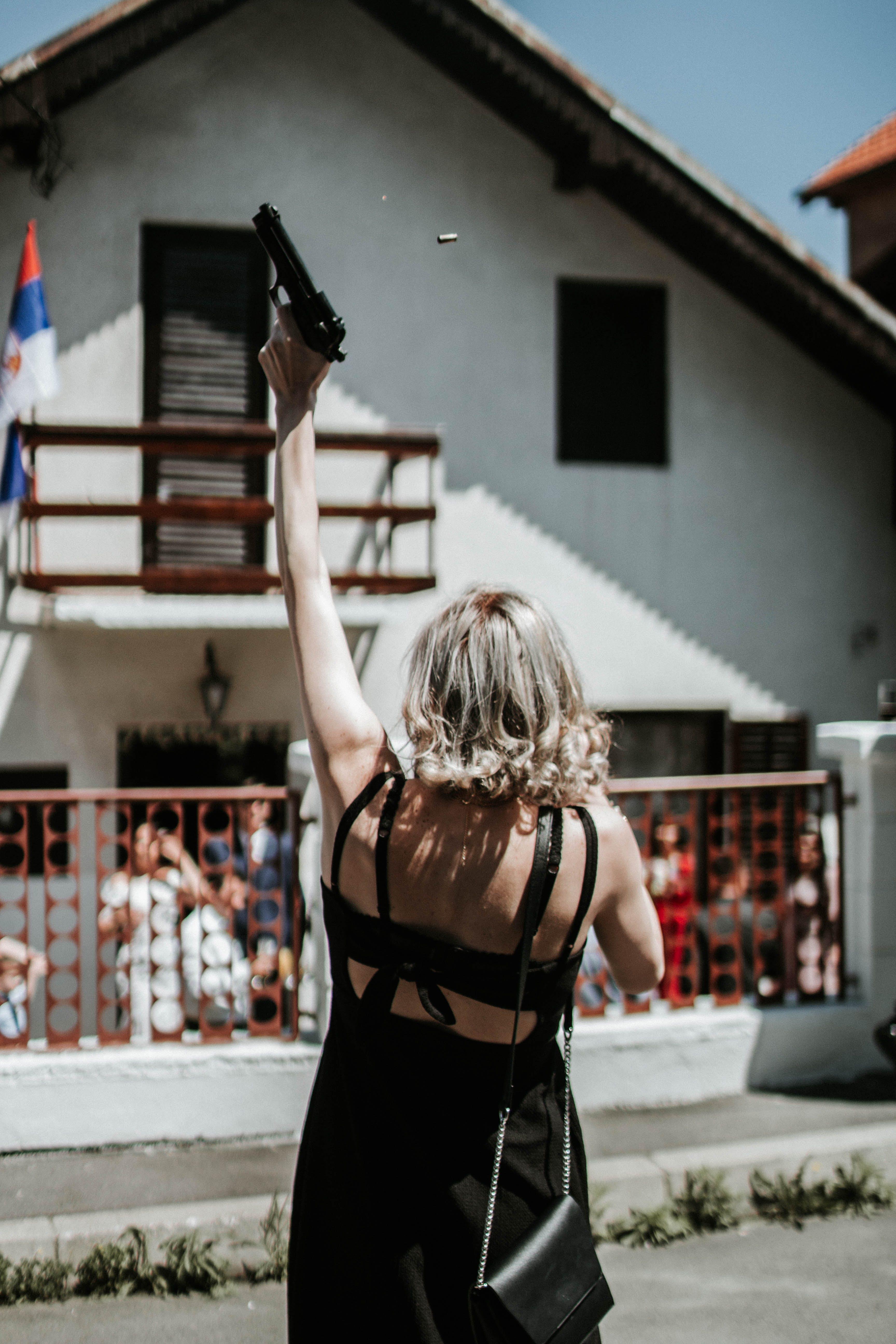 Woman In Black Mini Dress Holding Pistol