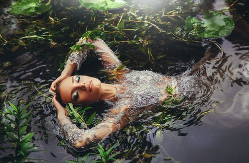 Woman In Long Sleeved Dress Surrounded By Water Plants
