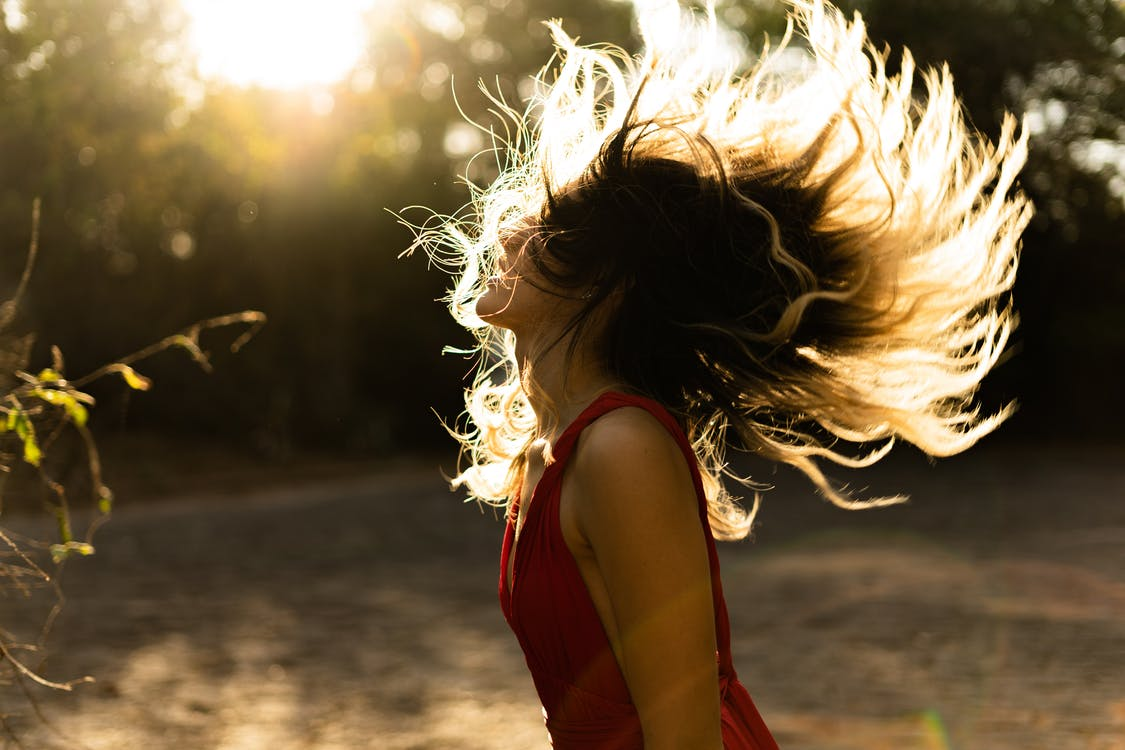 Woman in Red Sleeveless Top Flipping Hair