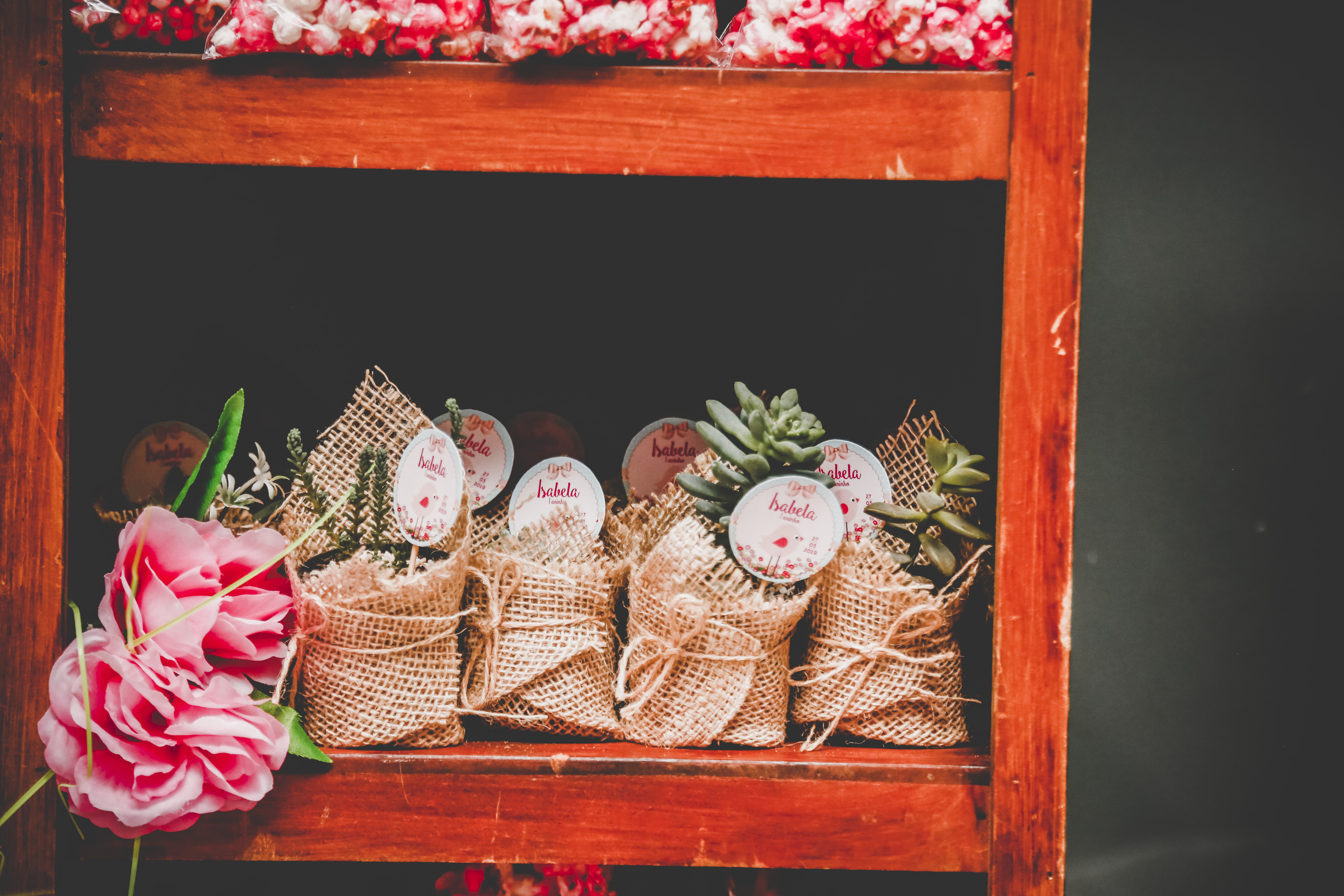 Brown Burlap Wrapped Party Favors on Brown Wooden Rack