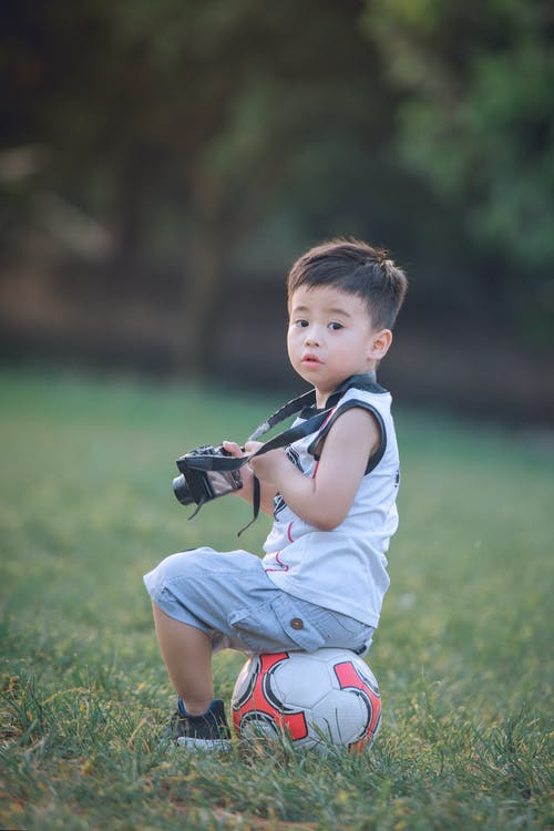 Boy Sitting On Soccer Ball Holding Dslr Camera