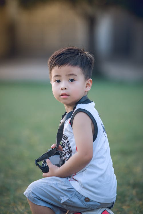 Boy Sitting on Ball With Dslr Camera