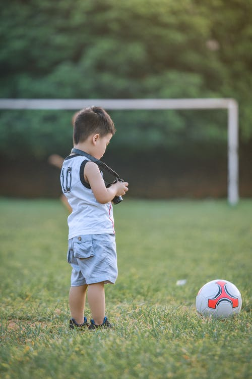 Boy Standing Using Dslr Camera Near Soccer Ball