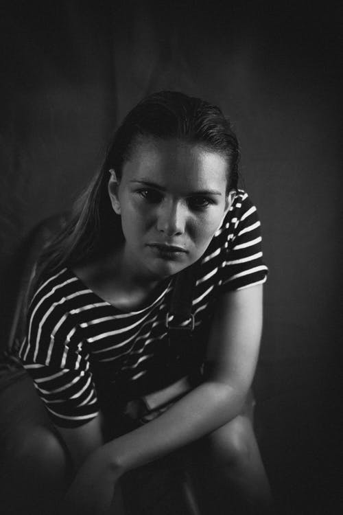 Grayscale Photo of Woman Posing While Sitting
