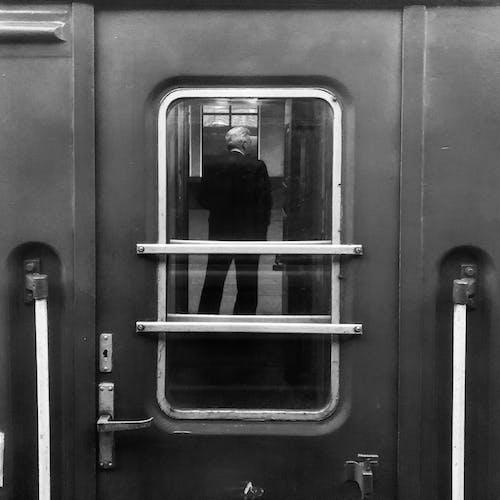 Closed Black Door With Mirror Showing Standing Man in Suit