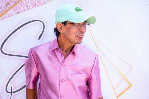Fotos de stock gratuitas de camisa rosa, de pie, gafas, gorro