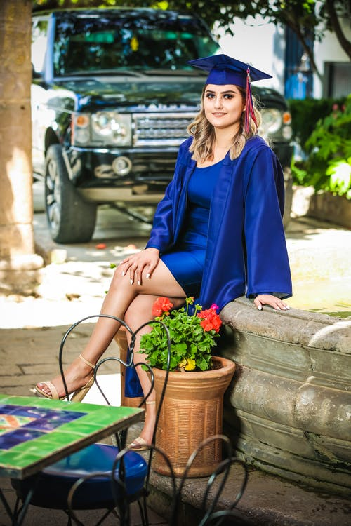 Woman Wearing Blue Graduation Gown Sitting Besides Potted Plant