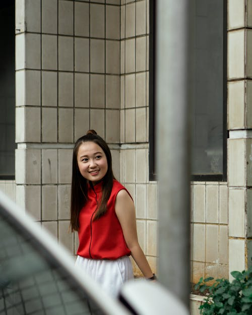 Photo of Smiling Woman in Red and White Outfit Leaning On Stone Wall Looking Away