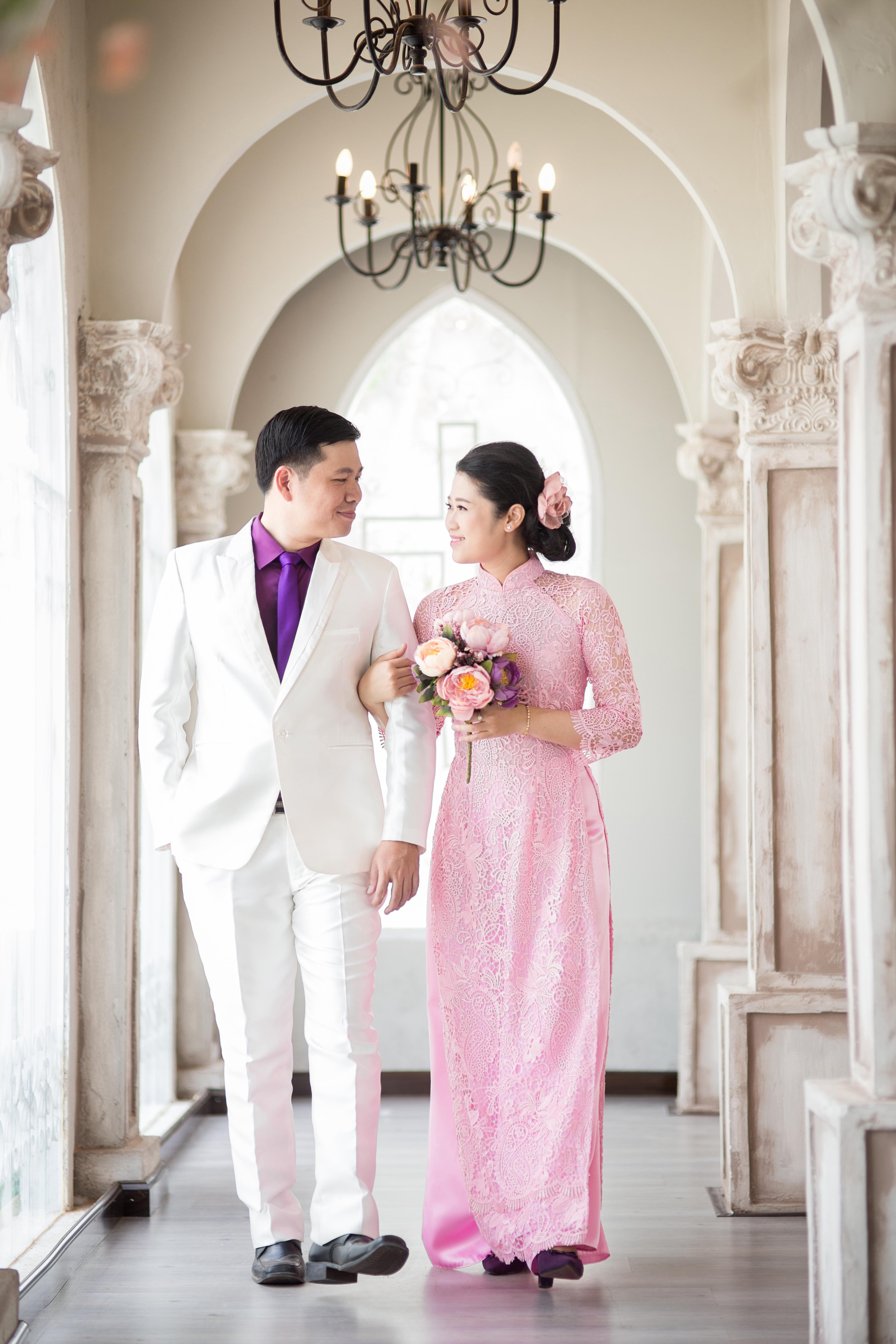 Man Wearing White Suit Jacket and Woman Wearing Pink Long-sleeved Dress Walking Corridor