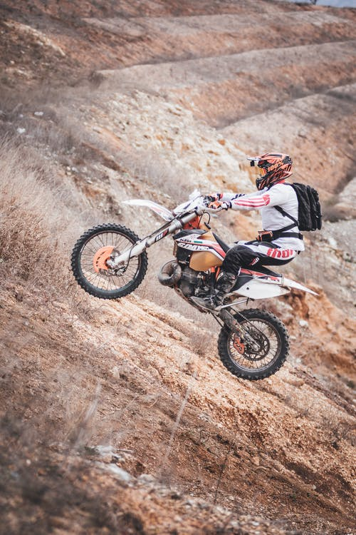 Person Driving Motocross Dirt Bike Outdoors