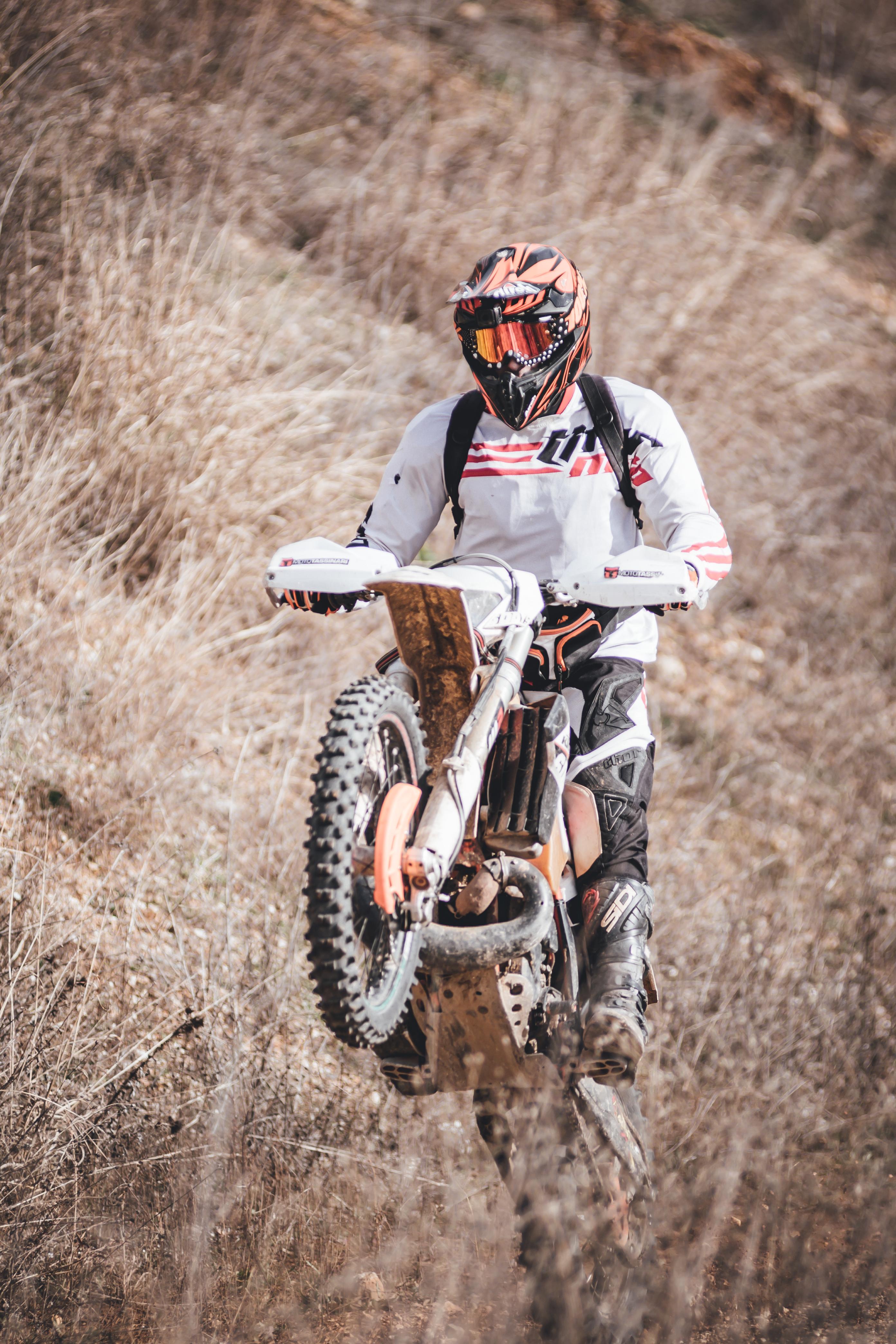 Person Riding White Dirt Bike Mid Air
