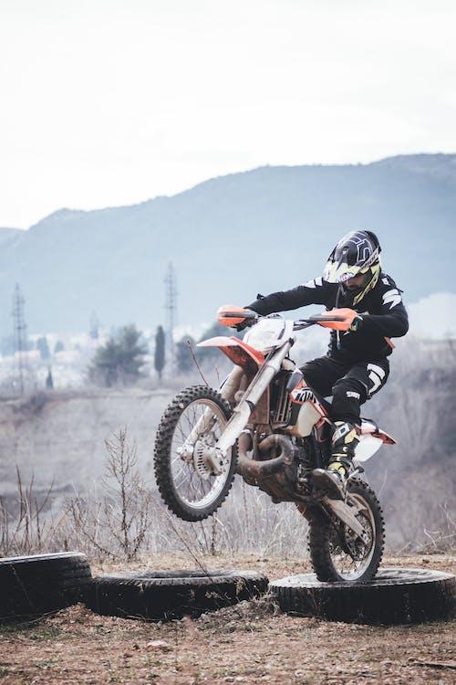 Person Riding Orange and White Dirt Bike