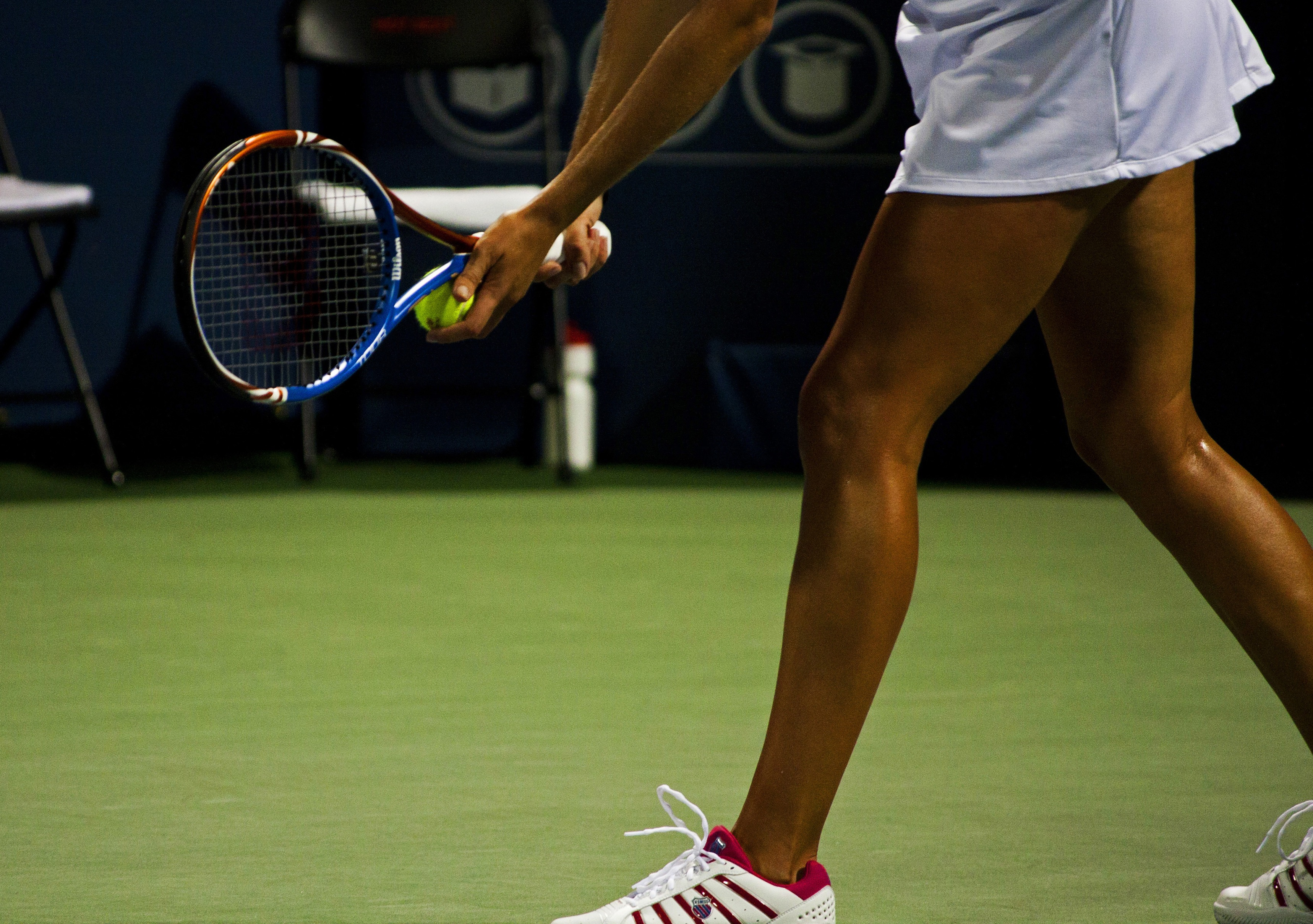 Woman Holding Red and Blue Tennis Racket in Field