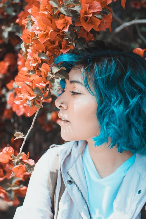 Side View Close-up Photo of Woman With Blue Hair Standing Under Orange Bougainvillea Flowers