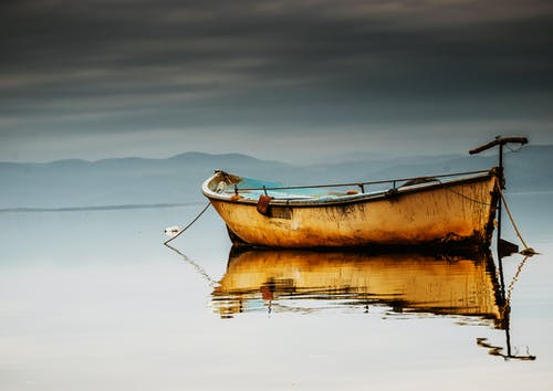 Brown Canoe on Calm Body of Water