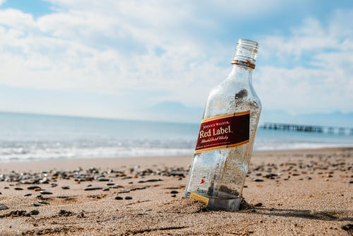 Red Label Glass Bottle on Brown Sand