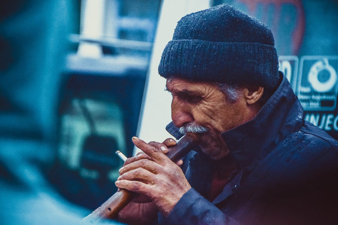 Person Holding Brown Smoking Pipe