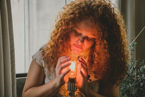 Woman Touching Light Bulb