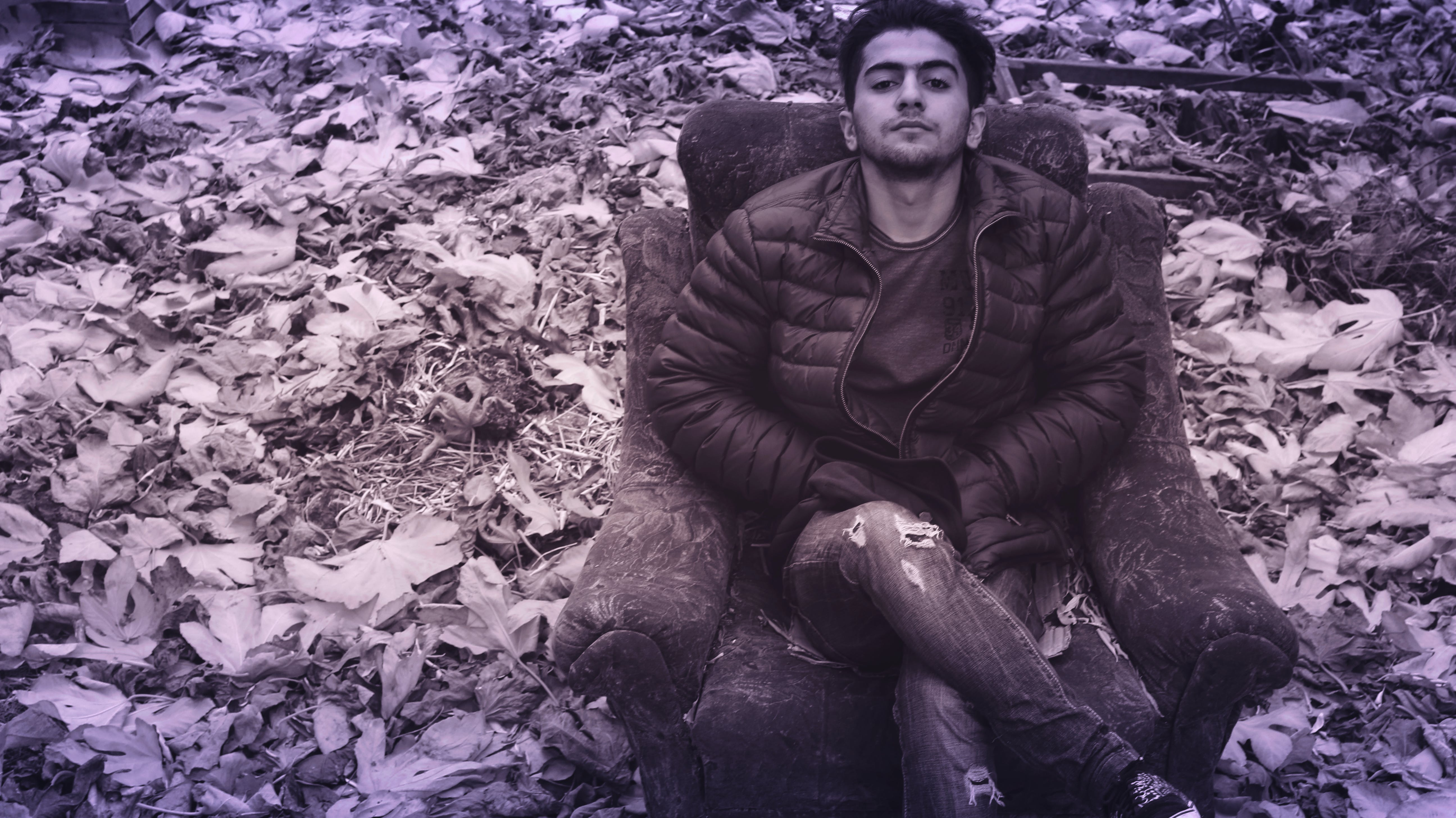 Man in Black Puffer Jacket and Distress Jeans Sitting in Couch