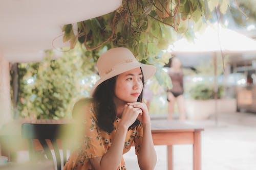 Woman Wearing Sun Hat Sitting Beside Table