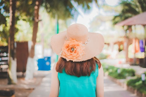 Back View Photo of Woman in Peach Sun Hat and Blue Top