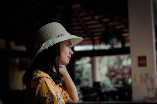 Side View Photo of Woman in Sun Hat Looking Out