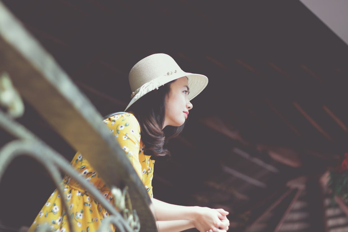 Photo of Woman in Sun Hat and Floral Dress Leaning on Metal Railing Looking Out