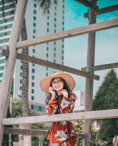 Photo of Smiling Woman in Sun Hat and Floral Dress Leaning on Wooden Structure