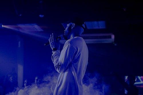 Foto profissional grátis de apresentação, azul, bomba de fumaça, cantor