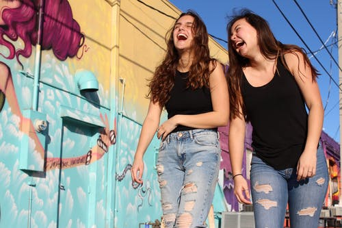 Photo of Two Laughing Women Walking Past Graffiti Wall