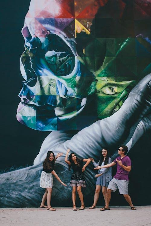 Group Of People Standing Beside Graffiti
