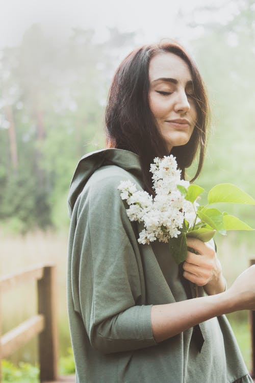 Photo of Woman With Her Eyes Closed Holding White Petaled Flowers