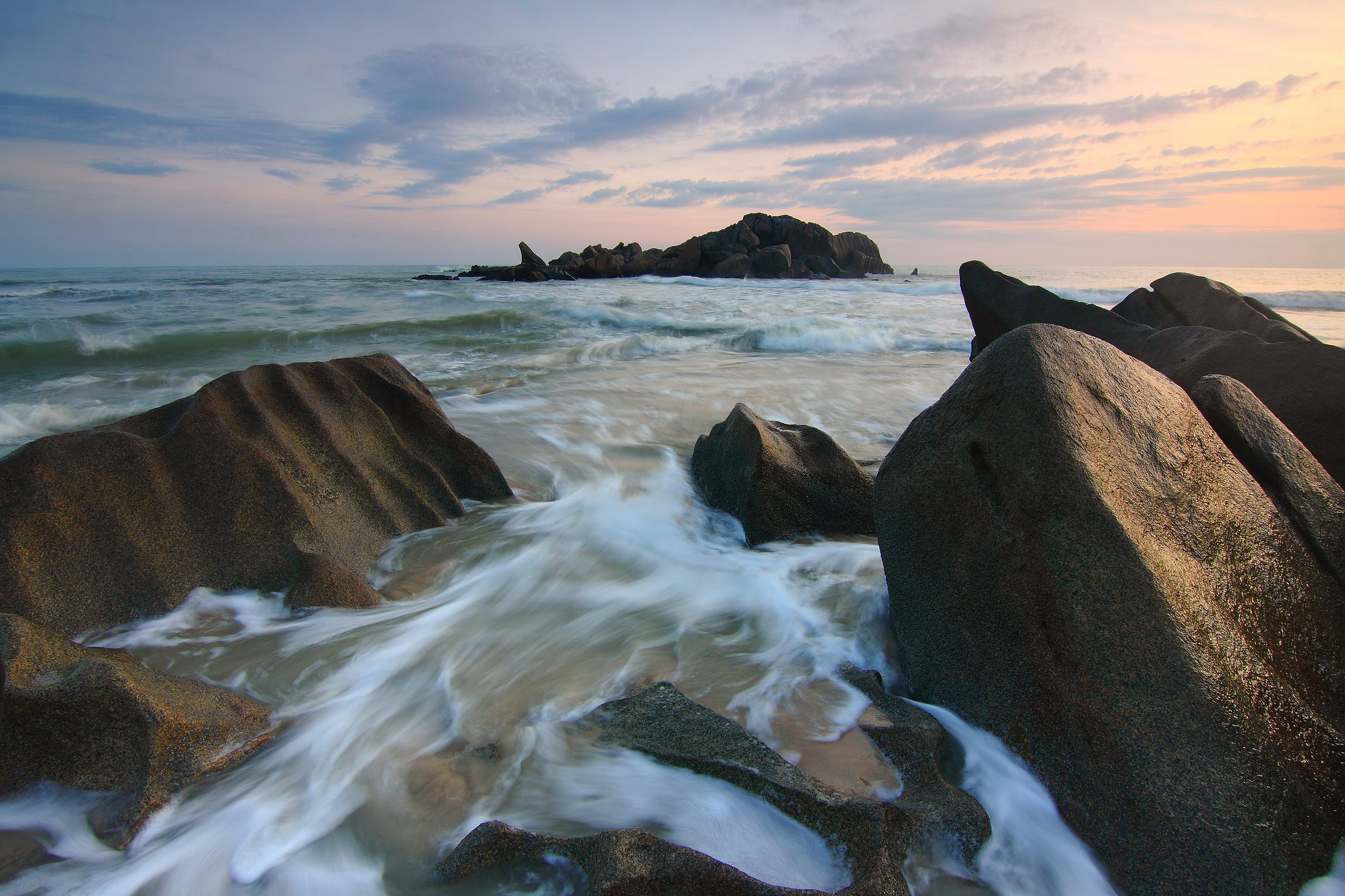 Sea Waves Crashing on Brown Boulders during Golden Hour Time Lapse Photo