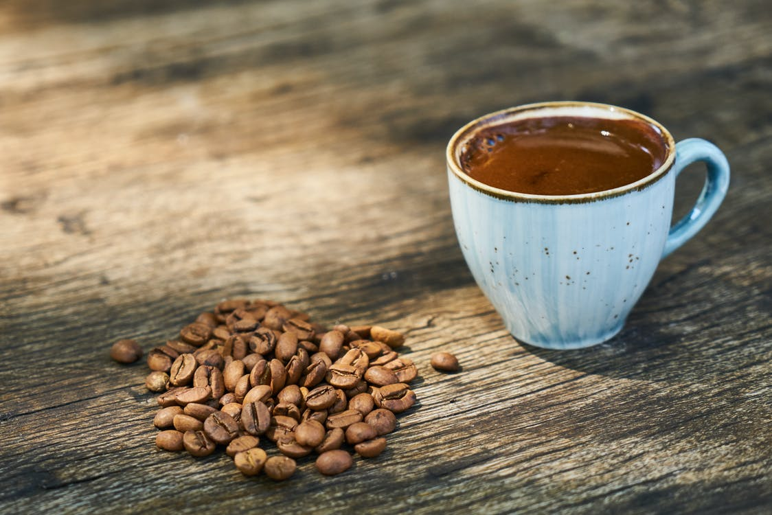 Cup Of Coffee Beside Coffee Beans