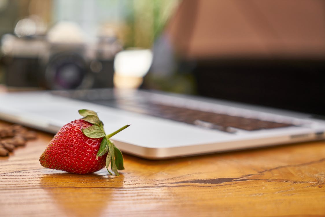 Close-Up Photo of Strawberry Near Laptop