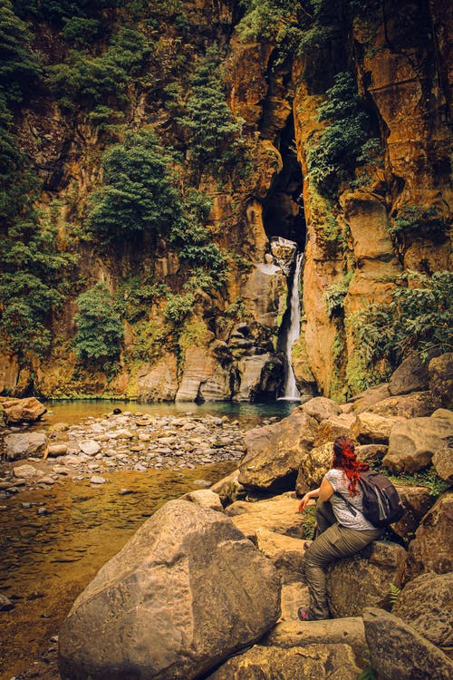 Woman Sitting On Big Rocks