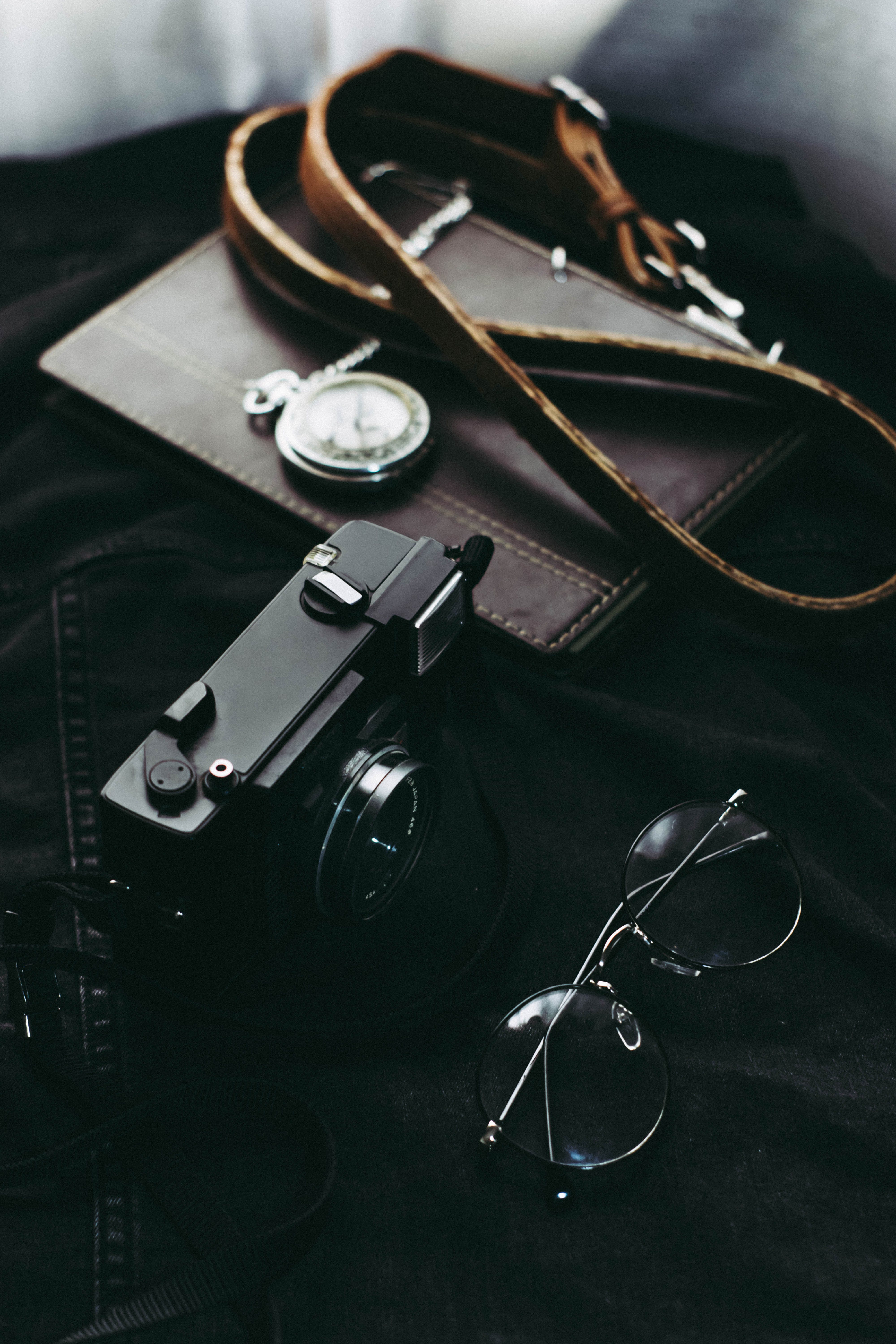 Black Camera Beside Pouch and Eyeglasses