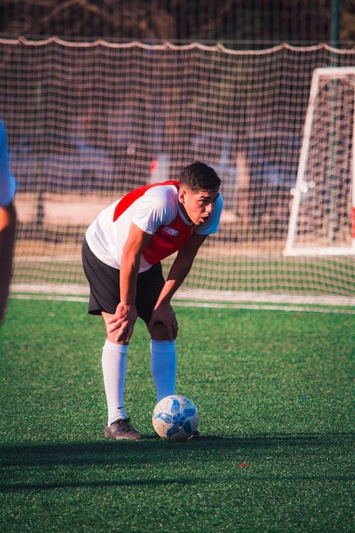 Man Standing Beside Soccer Ball On Soccer Field