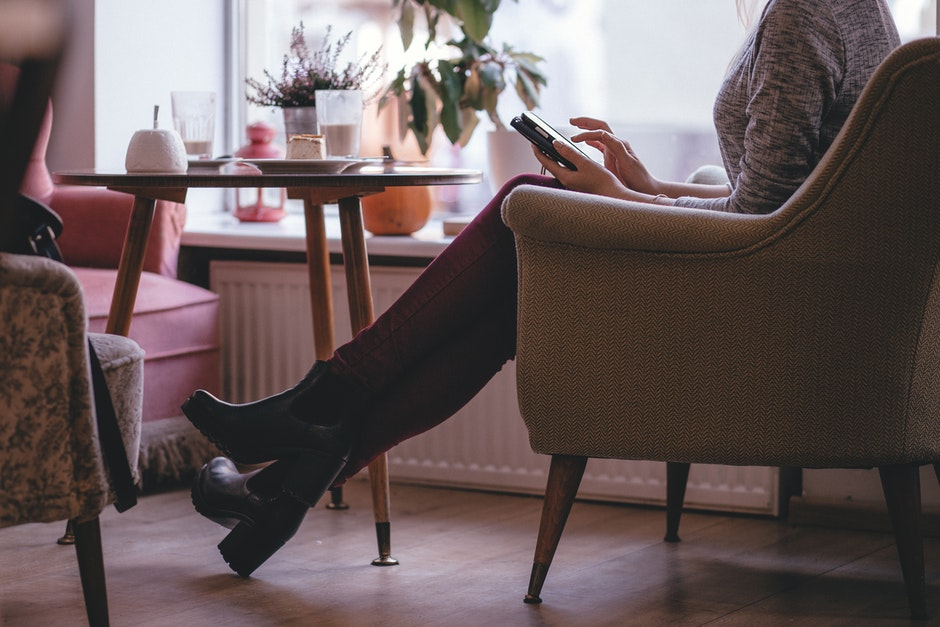 Woman Wearing Heather Gray Long Sleeve Top Red Fitted Pants and Chunky Boots Sitting on Sofa
