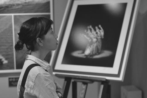 Grayscale Photo of Woman Standing Near Painting