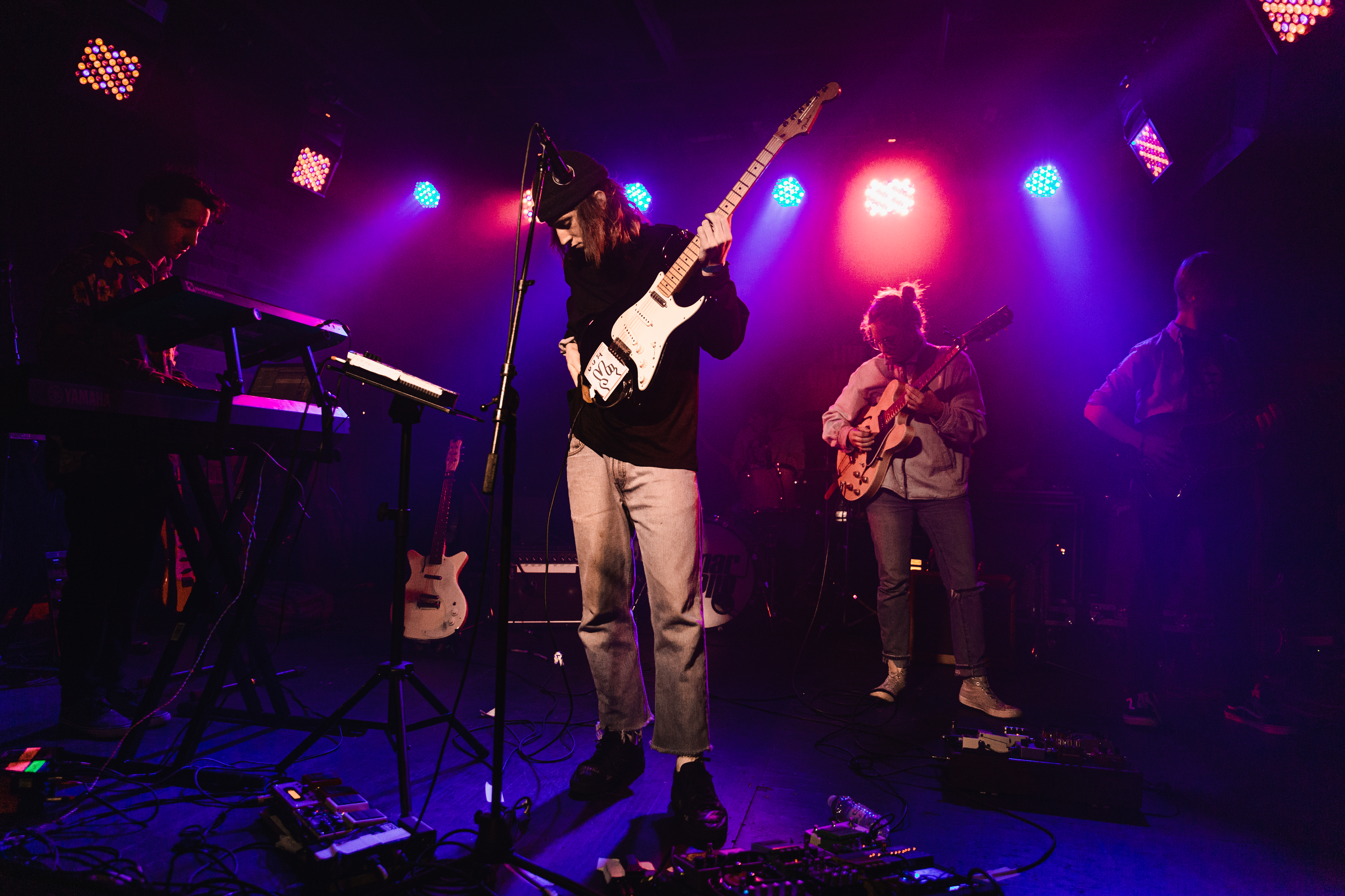 Group of People Performing on Stage Using Musical Instruments