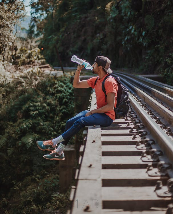 Man With Backpack Sitting  on Railroad and Drinks Water