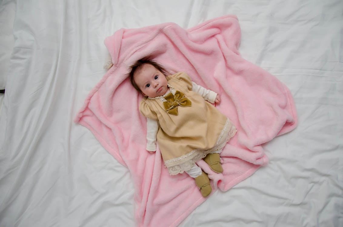 Baby in White and Yellow Dress on Pink Textile