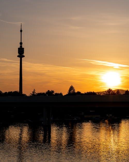Ilmainen kuvapankkikuva tunnisteilla appelsiini, auringonlasku, torni, vesi