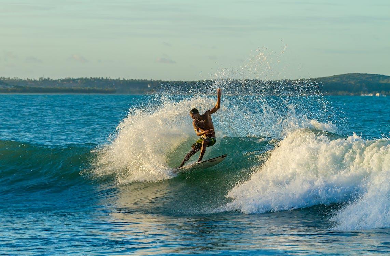 Topless Man Surfing on Sea