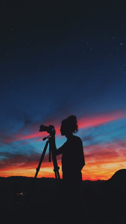 Silhouette of Person Looking at Camera on Tripod